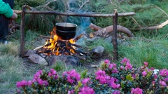 Cooking on a campfire in the mountains - stock footage