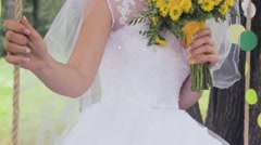 Beautiful bride in a veil rides a swing and smiles sweetly. The bride holds a Stock Footage
