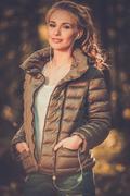 Beautiful teenage girl listens music outdoors - stock photo