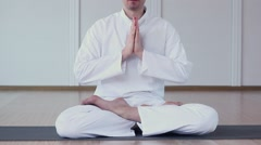 A Man Dressed in White Practices Yoga. He Folded his arms and namaste - stock footage