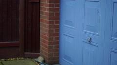 4K blue garage door opening to reveal buckets in fenced garden Stock Footage