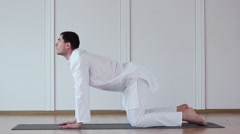 Cute Guy Doing Yoga. He Sits in a White Suit. Marjari Asana - stock footage