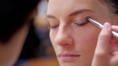Makeup brush on eye and people in background closeup - stock footage