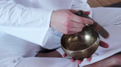 Handsome man is playing on Tibetan bowls and meditates. He sits in a white Stock Footage