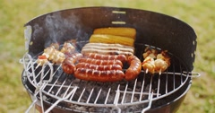 Sausages  corncobs and kebabs grilling on a BBQ Stock Footage