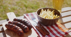 Three tasty smoked grilled sausages with chips Stock Footage