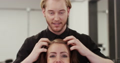 Stock Video Footage of Attractive woman smiling while having a consultation with her hair stylist. Shot