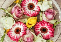 Roses and gerberas flowers in the glass bowl with water, holiday symbol - stock photo