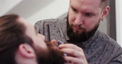 A male client having his moustache and beard groomed at a salon. - stock footage