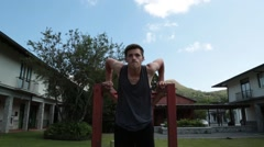 Front view of man using monkey bars on park to do dips Stock Footage