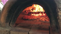 Two pizzas being turned in front of flame in stone oven  4K Stock Footage