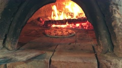 A pizza being turned in a stone oven  4K Stock Footage