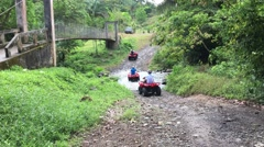 Group of 4-wheelers driving down old dirt road Stock Footage