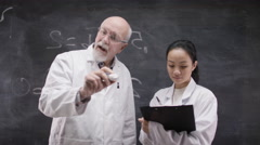 4K Scientists in white coats writing math formulas on glass screen in front of c Stock Footage