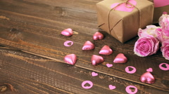 Pink roses and gift wrapped in recycled paper on rustic wood table. Stock Footage
