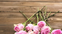 Stock Video Footage of Pink roses on rustic wood table.