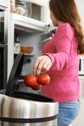 Stock Photo of Woman Throwing Away Out Of Date Food In Refrigerator