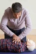 Man Using CPR Technique On Dummy In First Aid Class - stock photo