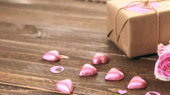 Pink roses and gift wrapped in recycled paper on rustic wood table. - stock footage