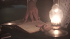 Hands Thumb Through the Book Near an Oil Lamp Stock Footage