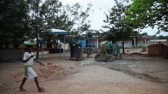 OUTSIDE PAKRO SCHOOL: CEMENT MIXER AND POLYTANKS Stock Footage