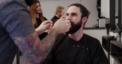Stock Video Footage of A  man looks into a mirror after having his beard groomed at a barber shop.