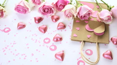 Pink roses and hand crafted gift bag on a white background. - stock footage