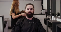 Stock Video Footage of Man looking into the mirror after having his hair groomed in a salon.