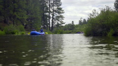 Rafts float smoothly down a river - stock footage