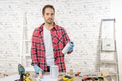 smiling young man with aerosol paint - stock photo
