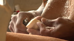 Close up of a craftman's hands working on a tupilak of bone Stock Footage