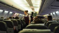 Stewardess at work in flying aircraft cabin Stock Footage
