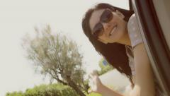Beautiful girl with sun glasses smiling from car window vintage look Stock Footage