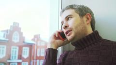Cheerful young man with short beard speaking on his cellphone by the window Stock Footage