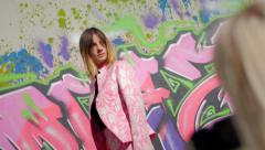 Model with pink dress posing in front of graffiti during a photo session - stock footage