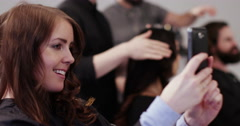 Stock Video Footage of Woman taking a self-portrait in coiffure studio. Shot on RED Epic.