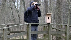 Ornithologist with binoculars and smartphone near bird cage Stock Footage