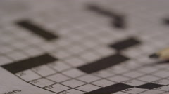 Close up of pencil on crossword puzzle - newspaper word game exercise - stock footage