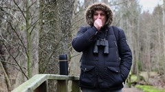 Ornithologist with binoculars drink tea on the bridge Stock Footage