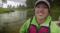 Stock Video Footage of Pretty young Asian woman rafts down a river in portrait
