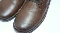 Close up of winter brown leather footwear rotating on white. - stock footage