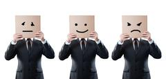 Businessmen holding a card with emotional face on white background. Clipping Stock Photos