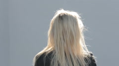 Blond woman in a black jacket turns around looks at camera and smiles Stock Footage
