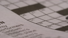 Close up of pencil on crossword puzzle - newspaper word game exercise Stock Footage