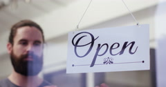 """Close-up of a young man turning over a """"Closed"""" sign . Shot on RED Epic. Stock Footage"""