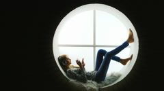 Attractive woman sitting at the round window, listening to music Stock Footage