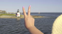 Woman Holds Up Peace Sign, From Moving Boat, To Lighthouse On Nantucket Island Stock Footage