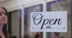 "Close-up of a beautiful young woman turning over a ""Closed"" sign . Stock Footage"