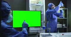 Scientist with protective suit and green screen Stock Footage