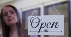 "Close-up of a beautiful young woman turning over a ""Closed"" sign . Shot on RED E Stock Footage"